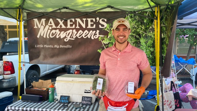 """A young man stands under his vendor tent at the San Marcos Farmers Market in front of a banner which reads """"Maxene's Microgreens Little plants, big benefits"""" and has a photograph of a bundle of small, leafy microgreen vegetables. The man holds two containers of different microgreen products in front of a table containing a large white cooler and two handwritten signs reading """"gut health"""" and """"heart health""""."""
