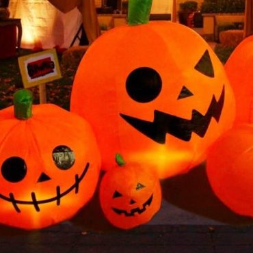 Inflatable jack-o-lanterns, all with different smiles, surrounded by various Halloween signs and decorations in a front yard.