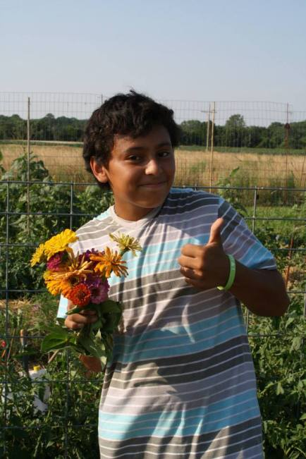 Trina McClure's son, Daniel, picks some flowers from the community plot - of course they're for his mom!