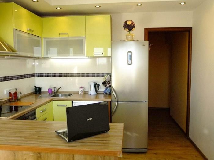 Справа от входа на кухню стоит холодильник