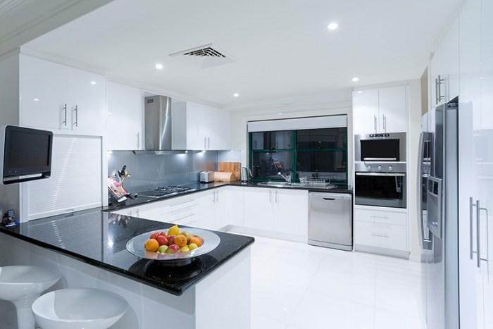 Белая кухня с большим кухонным гарнитуром по всему периметру
