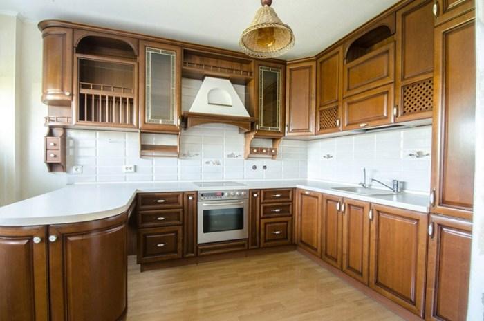 Классическая кухня из темного дерева с белым фартуком и столешницей