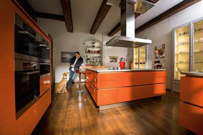 Просторная кухня-остров с белыми стенами и оранжевой мебелью