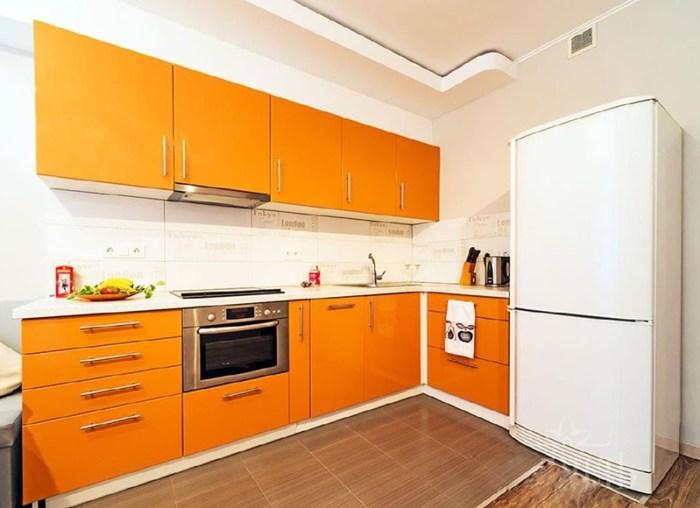 Оранжевый гарнитур на фоне белого помещения и холодильника