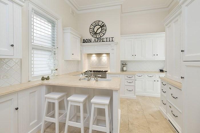 Часы с римскими цифрами на стене белой кухни