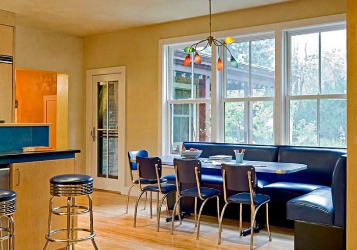 Угловой диван из синего кожзаменителя у большого окна