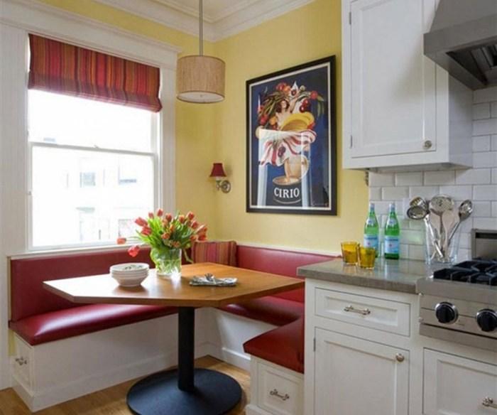 Красный диван между окном и кухонным гарнитуром