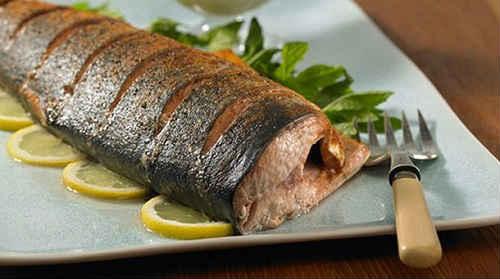 Fisk för att rensa av skalor, tarmar, klippa av fenor och huvud. Skär i portioner. Skär potatis och tomater i tunna cirklar, lök - i ringar eller halvringar. Skär fisken i portioner, salt och peppar efter smak. Förbered tre ark folie och forma fickor ur dem genom att stoppa kanterna. Smörj folien med vegetabilisk olja och lägg ut potatisen. Krydda med salt, peppar och strö över torkade örter. Toppa med skivor fisk och sedan lök. Häll gräddfil på toppen och lägg ut tomatskivorna. Krydda med salt och peppar. Vik in foliens kanter och baka i en ugn som är förvärmd till 180-190 grader i 40 minuter. Vik sedan ut folien, strö över riven ost och grädda i 10 minuter tills den är gyllenbrun. Strö den färdiga skålen med hackade örter.