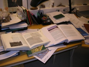 Så här ser mitt skrivbord ut för närvarande! Tillsammans med Frida ska jag skriva ihop rapporten över vindkraftsutredningen i Markbygden. Just nu är det mycket läsning av litteratur som gäller. Här på bild syns böcker om det första nybygget i Ersträsk, som sägs ha etablerats redan på 1600-talet i samband med silvergruvan på Nasa fjäll. Foto: Carina Bennerhag © Norrbottens museum