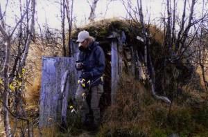 Åsa Lindgren kommer ut ur en torvkåta i grå jacka och gröna byxor. Fotograf Olof Östlund