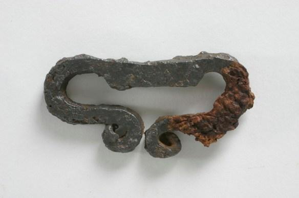 En av gravgåvorna – ett eldstål fotograferat vid konservering (2004). Till höger ses en bit tyg som rostat fast, och därmed bevarats.