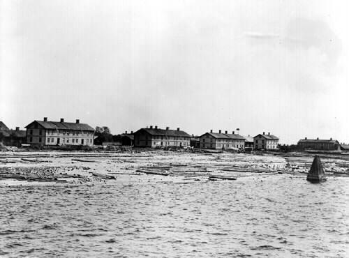 Svartvitt foto med fem hus, samt timmer i vatten