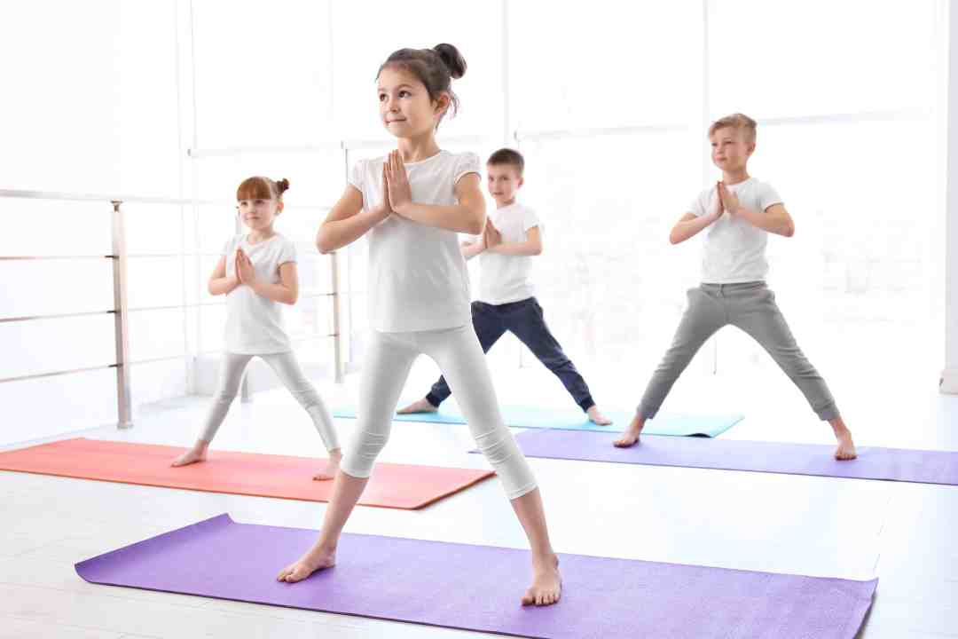 Four kids are practicing a wide legged yoga stance on yoga mats with hands at heart center