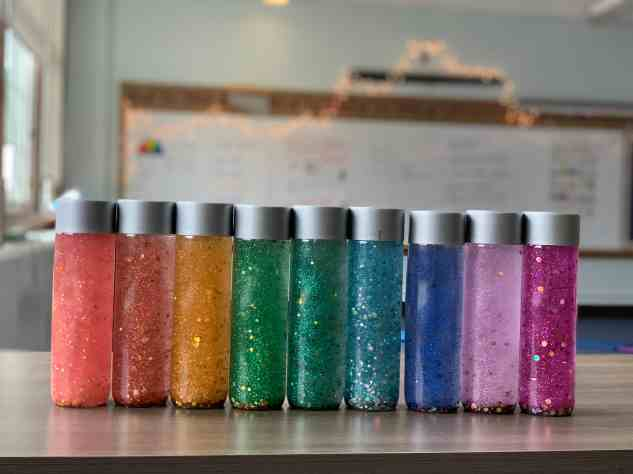 rainbow of glitter calming mindfulness jars lined up in a row