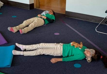 two kids laying and resting in savasansa pose doing yoga in class