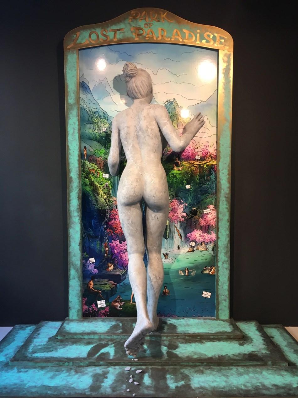 Installation von Phillippe Shangti im Pavillon von Andorra. Frauenskulptur aus Stein tritt durch ein Fenster in eine paradiesische Insellandschaft.