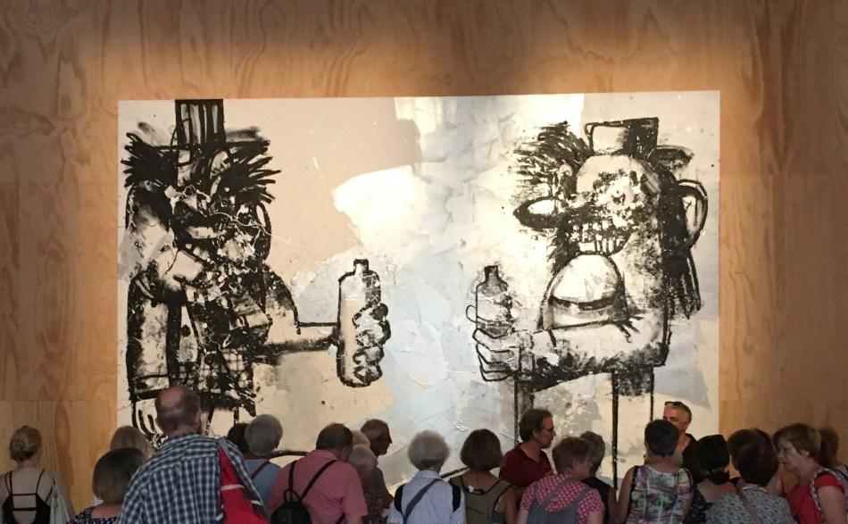 Zu sehen ist ein großformatiges Gemälde von George Condo. Darauf abgebildet sind zwei Männer mit einer Flasche in ihrer Hand. Sie sind einander zugewandt und scheinen sich zuzuprosten.