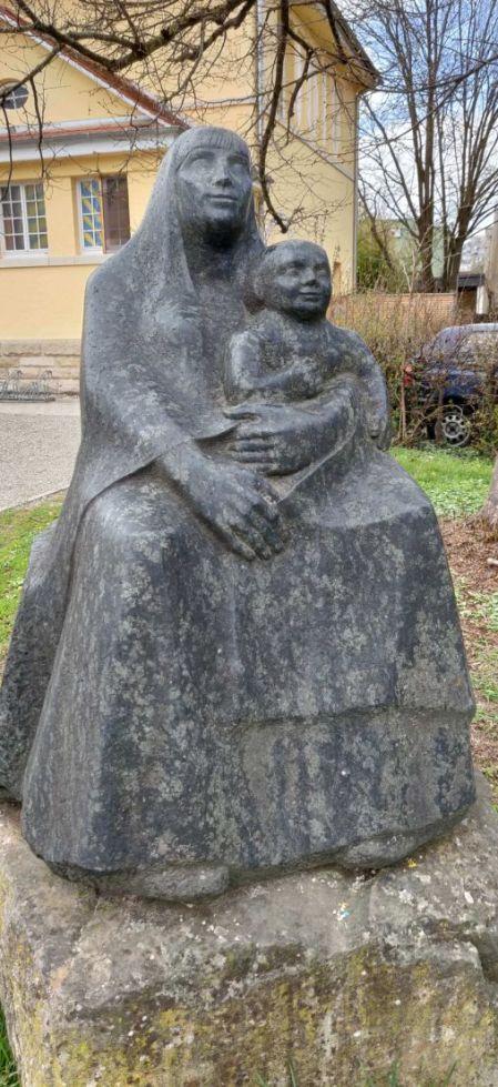 Wilhelm Pfeiffers Skulptur Mutter mit Kind aus dunklem Stein. Die Mutter sitzt aufrecht, ihr linker Arm liegt um das Kind im Schoß. Sie trägt einen Schleier und Umhang.