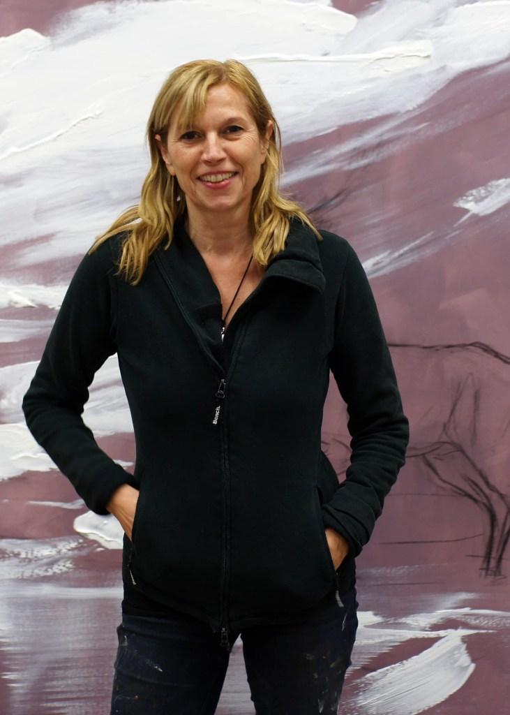 Vor einer großen Leinwand steht die Künstlerin Sigrid Nienstedt.