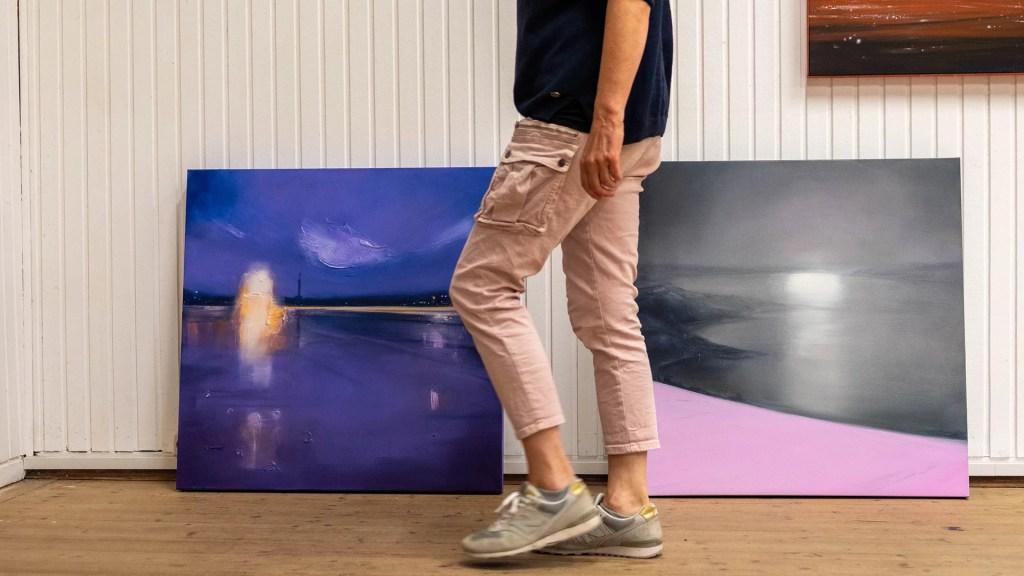 Sigrid Nienstedt läuft an zwei auf dem Boden stehenden Werken vorbei.