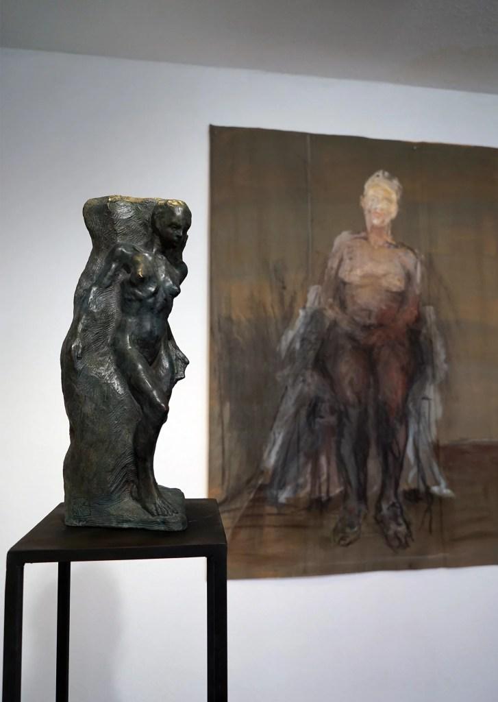 Aus einem Brozeklotz scheint eine weibliche Figur heraus zu treten. Im Bildhintergrund hängt eine Malerei, auf dem ein weiblicher Akt dargestellt ist.