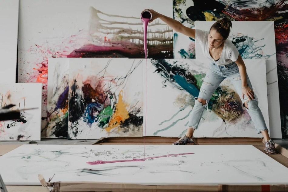 Felisa Rauschenberger in ihrem Atelier vor Leinwänden. Die Künstlerin schüttet Farbe aus einem Eimer auf die Leinwand.