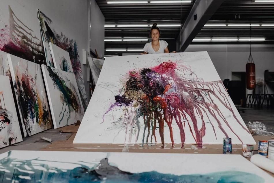 Felisa Rauschenberger in ihrem Atelier. Sie hält eine frisch bemalte Leinwand in ihren Händen.