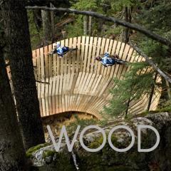 WOOD - Dos personas en bicicleta por una pasarela de madera en un bosque