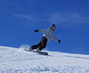 Una persona descendiendo snowboard