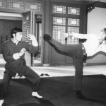 Carter Wong blocks a round house kick from Chuck Norris