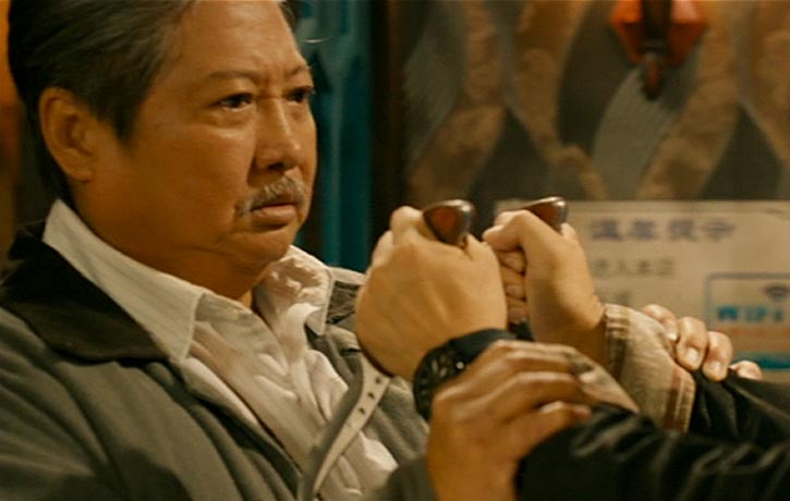 Ding Hu restrains his knife-wielding adversary