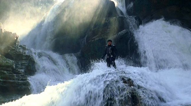 Jackie really does stand in the middle of a raging waterfall!
