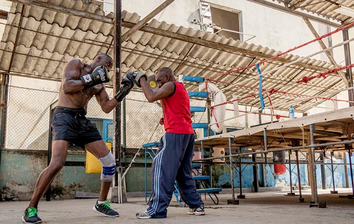 Putting power in his punches, Idris and coach Nardo Flores practice with the pads