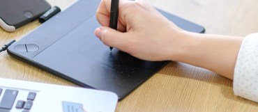 Grafisk formgivare med ritplatta som ger tips