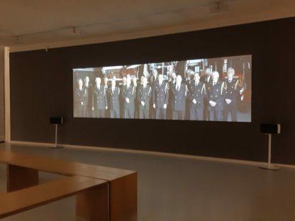 Simone Bennett Film Dordrechts Brandweer koor die een compositie uitvoert van Peter Vandrie over de Branddriehoek (brandstof, zuurstof, temperatuur).
