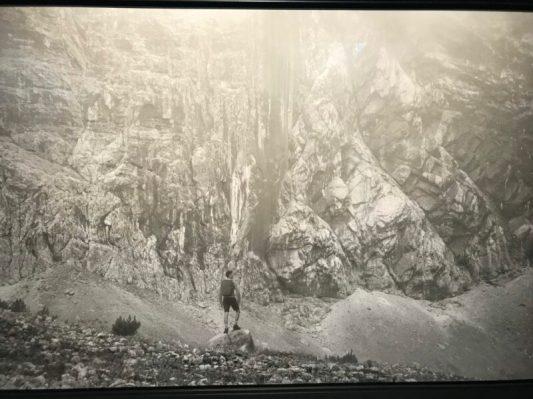 """Erwin Olaf, Vor der Felswand, Kevin. """" .. daar staat de jongeman in korte broek, met opgeheven hoofd naar de bergwand te kijken. Kwam hij daar terecht nadat hij het bos inliep?"""""""