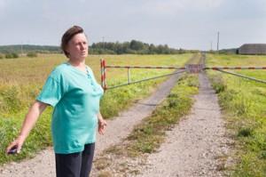 Krystyna Antul rozkłada bezradnie ręce przed szlabanem blokującym zjazd z szosy na drogę prowadzącą do jej domu Fot. Marian Paluszkiewicz