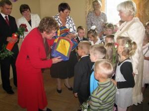 Mer rejonu wileńskiego Maria Rekść wręcza najmłodszym uczniom wyprawki szkolne.