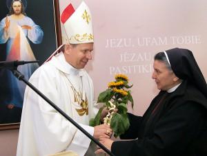 Siostra Michaela wręcza arcybiskupa Gruszasa złociste słoneczniki Fot. Marian Paluszkiewicz