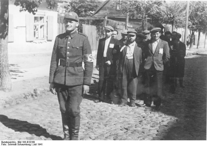 Litewski policjant nazistowski w Wilnie prowadzący grupę żydowskich robotników (1941) Fot. Wikipedia
