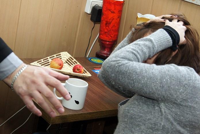 Kobieta w szarym swetrze próbuje bronić się przed przemocą domową