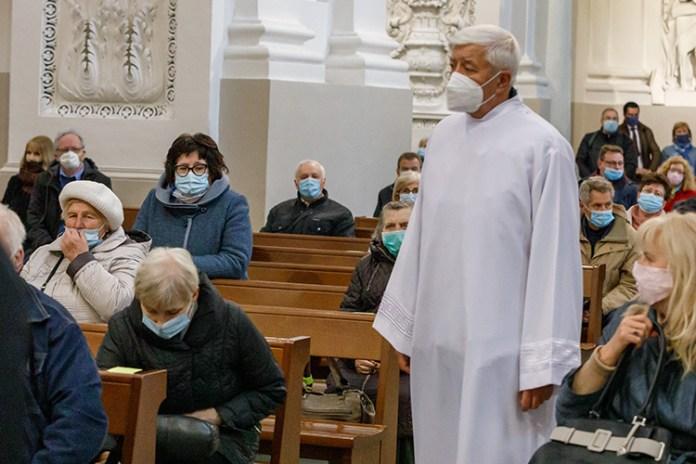 Starsi ludzie w maskach siedzą w kościele pomimo pandemii