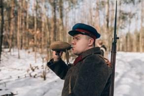 Młody mężczyzna przebrany za żołnierza Armii Czerwonej pije wodę z manierki