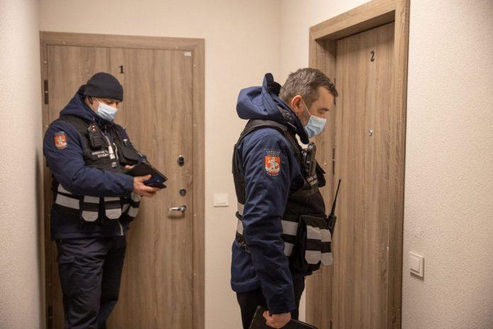 Dwóch policjantów w mundurach i maskach puka do drzwi mieszkania