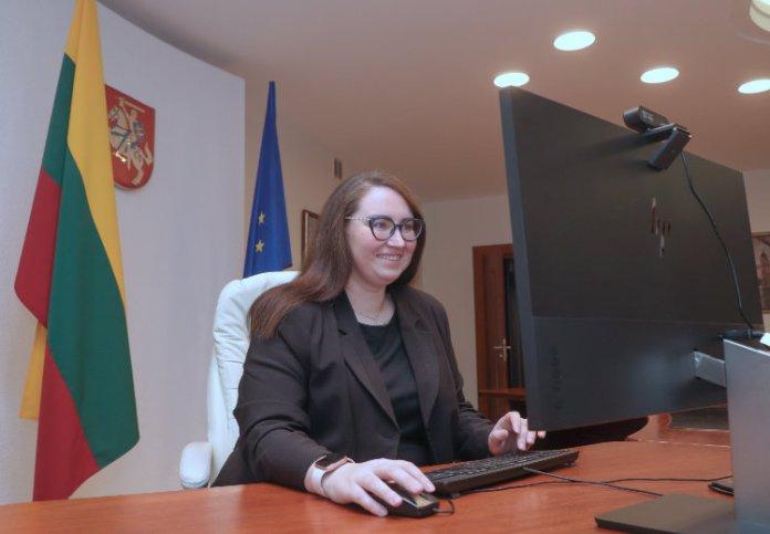 Ewelina Dobrowolska siedzi w białym fotelu, uśmiecha się do komputera trzymając niepewnie myszkę komputerową i naciskając przyciski na klawiaturze.