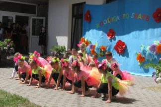 Dzieci w różowo-żółtych strojach biorą udział w obchodach Dnia Rodziny w Domu Wspólnoty w Rukojniach