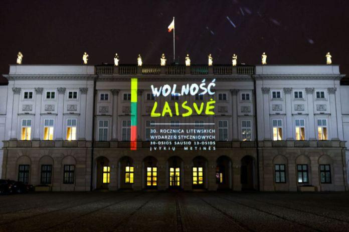 """Pałac prezydencki w Warszawie oświetlony napisami """"laisvė"""" i """"wolność"""" przypominając o bohaterach 13 stycznia 1991 roku."""