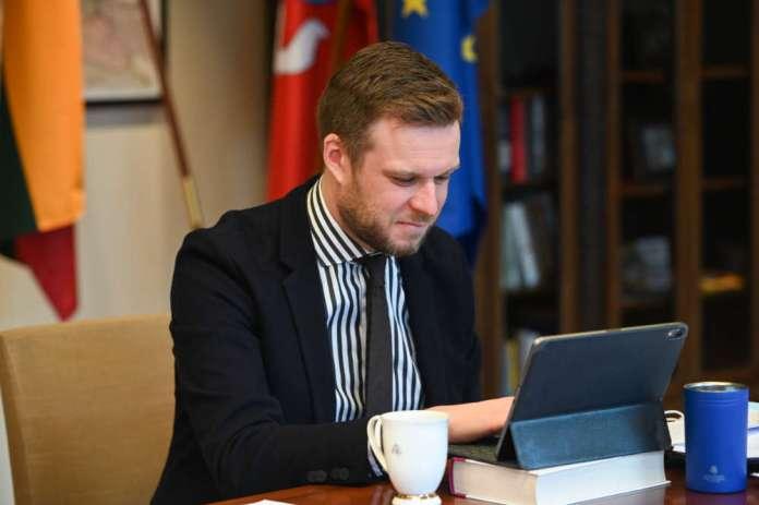 Gabrielius Landsbergis siedzi przed tabletem i się uśmiecha z lekkim niesmakiem.