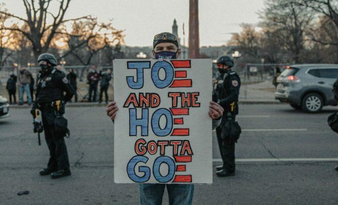 Mężczyzna będący zwolennikiem Donalda Trumpa trzyma transparent sugerujący, że Joe Biden oraz Kamala Harris powinni odejść z polityki