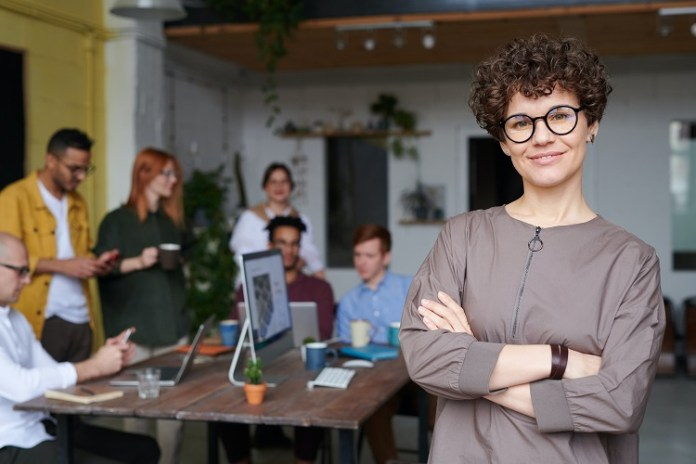Kobieta w kręconych włosach i okularach stoi przed zespołem pracującym przy stole